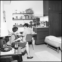 Two female students in a residence room, one raising a teacup to take a drink.