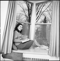 Female student, wearing slippers, sitting in a windowsill in residence dorm room.