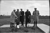 Five men, using three shovels at the sod turning, Murray Ross (left end) and Robert Winters (centre).