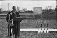 Robert Winters at a microphone, four ceremonial shovels on the right and a construction notice in the background.