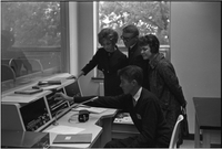 Three students look on while another operates audio controls.