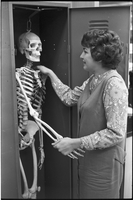 Student, Linda Robinson, shaking hands with a skeleton in a locker.
