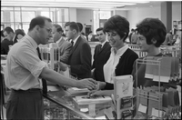 Man at the bookstore counter assists two female students.