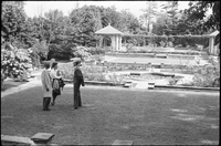 Two men and a woman in the formal garden at Glendon Hall.