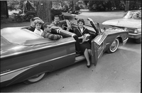 Five students in a convertible with the passenger door open.