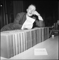 A male student leaning on top of a row of books with a York opening programme in his hand.