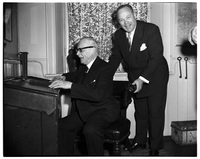 Prime Minister St. Laurent seated at desk flanked by Toronto Mayor, Allan Lamport