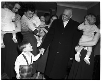 Prime Minister St. Laurent with mothers and children, holding hand of young child