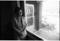 Mrs. Charles Whalen, standing in profile by a window