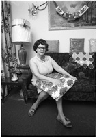 Mrs. Charles Whalen, seated on couch, holding a wrapped package