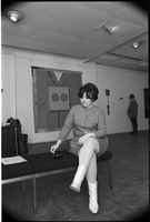"Joyce Wieland seated on a bench in front of her hanging ""The Camera's Eyes"" other pieces ""Home Work"" and ""Don't Mess with Bill (for Anita and Sylvia)"" are in the right background at The Isaacs Gallery."