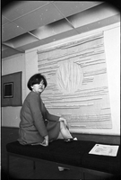 "Joyce Wieland seated on a bench in front of her untitled '66 [cotton hanging] another piece ""Film Mandala"" visible in left background at The Isaacs Gallery."