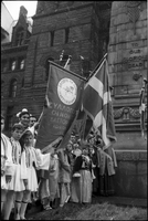 Children, in Greek national costume, standing in front of the cenotaph at Old City Hall; banner and flag with Greek writing