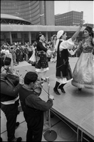 Musicians play, while female Greek dancers in costume, perform on stage at Nathan Phillips Square outside Toronto City Hall