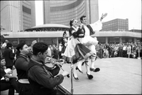 Musicians play, while Greek dancers in national costume, perform on stage at Nathan Phillips Square outside Toronto City Hall