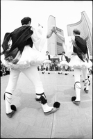 Young men, in fustanella costumes, dancing on stage, in front of crowd gathered in Nathan Phillips Square