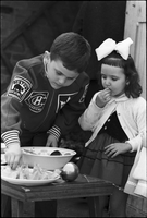 Boy and young girl eating sliced fruit as part of Easter celebrations.
