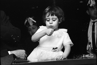 A young girl, blows on her hand, at The Achaian Society's third annual masquerade ball