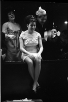A young woman sits above the edge of the dance-floor, singer in background, at The Achaian Society's third annual masquerade ball [broken negative]