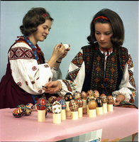 Two young women, in Ukrainian dress, demonstrate dyeing Easter eggs.