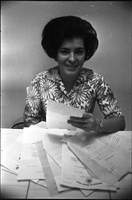 Juliet Lopes, seated, with paperwork.