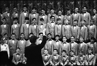 Close up of choir in performance, conductor in foreground.
