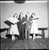 Two women, each holding a proposed plot plan for the Alexander-Wellesley redevelopment, and two men in suits, pose in front of a table.