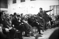 Man wearing leather jacket, gestures with his left arm, at community meeting of Alexandra Park residents in the gymnasium of Ryerson Community School.