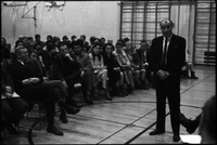 Man wearing suit, hands clasped, at community meeting of Alexandra Park residents in the gymnasium of Ryerson Community School.
