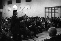 Man wearing leather jacket, gestures with his right arm, at community meeting of Alexandra Park residents in the gymnasium of Ryerson Community School.
