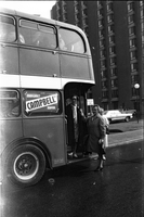 Two older women boarding the back of a double decker bus that will take Alexandra Park residents to a Food City supermarket outside their neighbourhood; a Margaret Campbell for mayor election sign is visible.