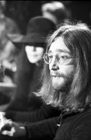 John Lennon speaking to the media, Yoko Ono is out of focus in background [at Ontario Science Centre].