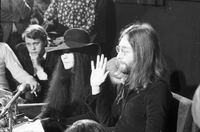 Yoko Ono and John Lennon (raising his hand) at a press conference at the Ontario Science Centre.