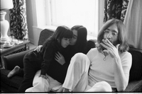 John Lennon, Yoko Ono and her daughter, Kyoko Chan Cox, seated on couch in their suite at the King Edward Hotel; Lennon is taking a drag on his cigarette.