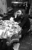 "John Lennon, elbow propped on table holding a cigarette, at the home of Ronnie Hawkins; table contains teapot, teacups, remnants of a meal, ""War is Over"" handbills and an ashtray."