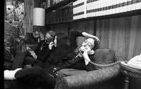 Ronnie Hawkins (on the telephone and writing), Yoko Ono (holding a cigarette), and John Lennon (on the telephone) sitting on a couch Hawkins' home.