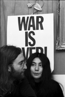 "John Lennon (in profile) and Yoko Ono in front of a ""War is Over if You Want it"" poster at the home of Ronnie Hawkins."