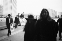 John Lennon and Yoko Ono, walking past fans with signs, on their way to the Ontario Science Centre.