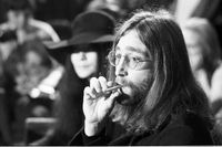John Lennon smoking a cigarette, Yoko Ono is out of focus in background [at Ontario Science Centre].