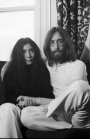 John Lennon, seated cross legged on a chair, with his hands in Ono's lap [at King Edward Hotel].