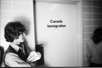 A John Lennon fan standing next to Canada Immigration door with his arms crossed.