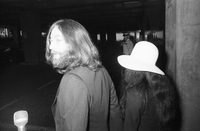 John Lennon and Yoko Ono walking togetherᅠ; Lennon is looking behind.