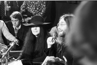 Yoko Ono and John Lennon (partially obstructed) at a press conference at the Ontario Science Centre.