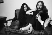 John Lennon and Yoko Ono seated, with Lennon scratching his nose [at Windsor Arms Hotel].