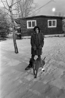 Woman, wearing snowshoes, with a Boxer dog on a leash.