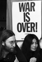 "John Lennon and Yoko Ono in front of a ""War is Over if You Want it"" poster at the home of Ronnie Hawkins."