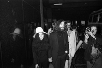 John Lennon and Yoko Ono walking hand in hand with a camera man beside them; their Canadian immigration lawyer, Alan Mintz, is visible in background (glasses and moustache).