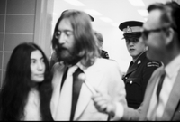 John Lennon and Ono leaving Immigration Office, with a reporter's microphone in Lennon's face, and RCMP officer in background.