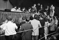 Image of The Beatles at a press conference inside Maple Leaf Gardens, a man is gesturing to reporters.