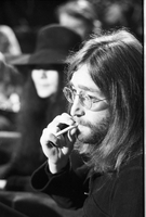 John Lennon with an unlit cigarette, Yoko Ono is out of focus in background [at Ontario Science Centre].